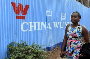 A woman walks past corrugated iron fencing at a Chinese construction site in Nairobi