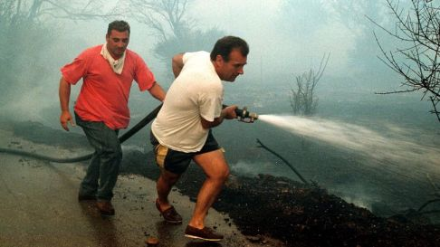ATH05 - 19980723 - ATHENS, GREECE : Local residents help the firemen to fight the fires as they come close to their houses in the eastern Athens suburb Anthousa on July 23. The fire started from the forest at the mountains of the region, but funned by very strong winds spread at Neos Vouzas, Kallitehnioupoli and Pikermi, burning private property . EPA PHOTO/LOUISA GOULIAMAKI